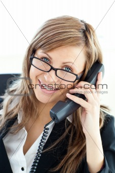 Assertive businesswoman talking on phone looking at the camera