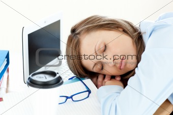Tired caucasian businesswoman sleeping on her desk