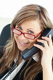 cheerful business woman with red glasses on the phone sitting in her office