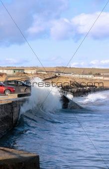 waves crashing against seaside wall