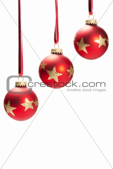 three hanging dull red christmas balls with golden stars