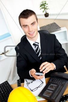 Positive businessman using his calculator looking at the camera