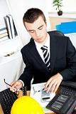 Serious young businessman using his calculator