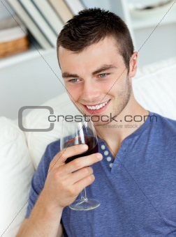 Animated young man drinking wine sitting on the sofa