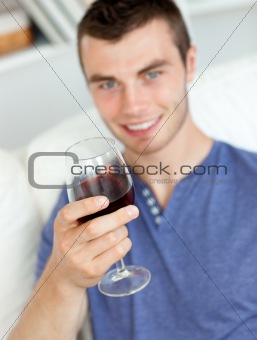 Charismatic young man holding a glass of wine sitting on a sofa