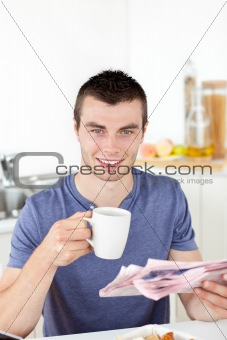 Positive young man holding a cup and a newspaper smiling at the