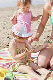 Sweet little girl using suncream at the beach