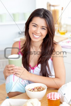 Beautiful asian woman having breakfast smiling at the camera