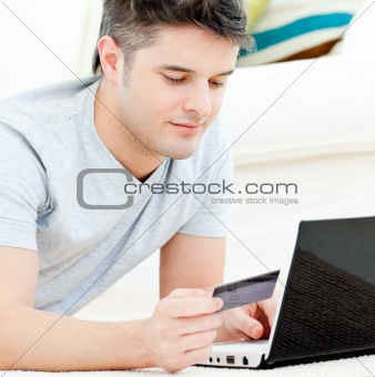 Positive young man holding a card using his laptop on the floor
