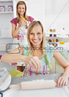 Animated female friends baking muffins smiling at the camera