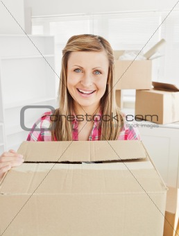 Positive woman holding a box standing in her new house looking a