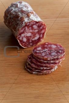 slices of an a italian salami on an oak table