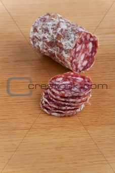 slices of an a italian salami on an oak table