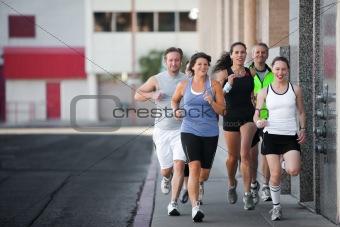Group of friends runs downtown.