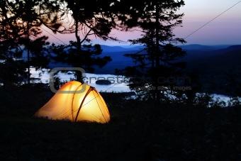 A tent lit up at dusk