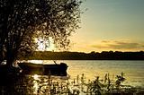 Beautiful sunset landscape with boat on lake