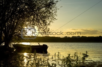 Beautiful sunset landscape with boat on lake