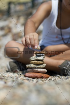 boy is making a pyramid of stones beside the sea