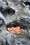 Nude woman sleeping on rock.
