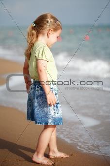 Small girl standing on beach