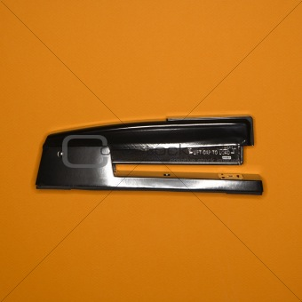 Stapler on orange.