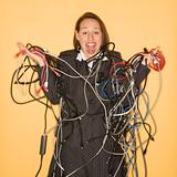 Businesswoman holding tangled cables.
