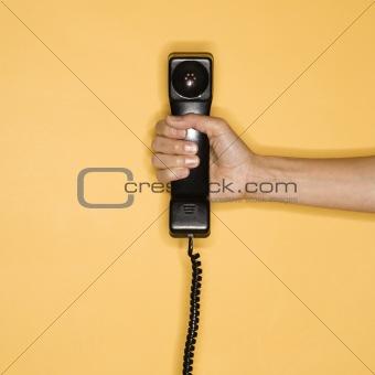 Hand holding telephone.