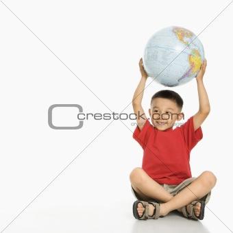 Boy holding globe.