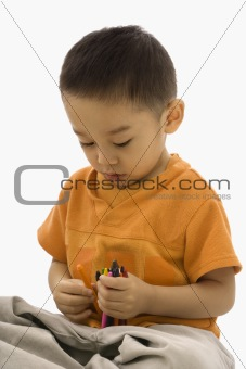Boy holding crayons.