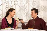 Couple toasting glasses at dinner.