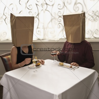 Couple dining wearing bags on heads.