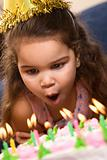 Girl blowing out birthday candles.