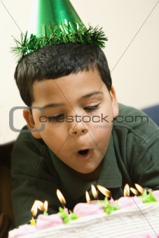Boy blowing out birthday candles.
