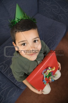 Boy holding birthday present.
