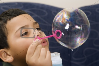 Boy blowing soap bubble.