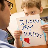Boy giving dad drawing.