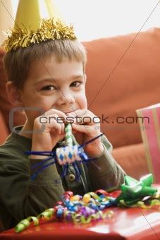 Boy blowing noisemaker.