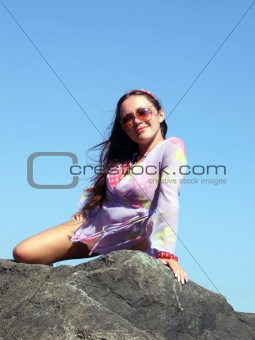 The sexual girl sits on a stone on a background of the sky