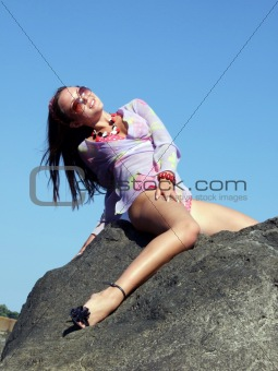 The sexual girl sits on a stone on a background of the sky2