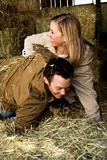 Couple playing in hay.