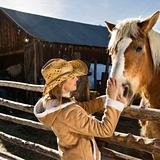 Woman petting horse.