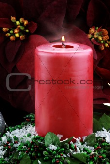 Lit Christmas Candle and Poinsettias