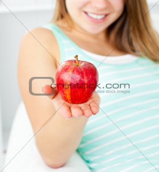 Cute young woman holding an apple in her hand