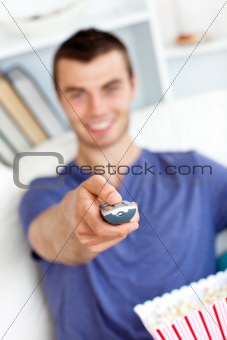 Positive caucasian man holding a remote looking at the camera in