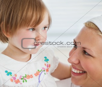 Caucasian cute girl brushing her teeth with her mother