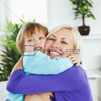 Attentive mother hugging her little daughter