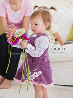 Adorable little girl holding flowers in the living-room