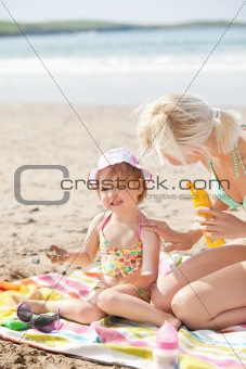 Crying little girl at the beach with her mother
