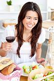 Captivating asian woman holding a wineglass eating a salad at ho