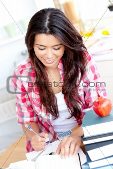 Positive asian student doing her homework at home